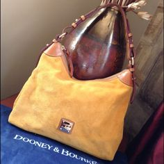 "Dooney & Bourke Suede Hobo Like New Gorgeous, suede hobo from Dooney & Bourke. Palomino suede exterior and red, cotton interior are both clean. Brown leather handle and trim are in excellent condition. Interior has one snap pocket, one slam slash pocket, one large slash pocket, one zippered pocket and a key leash. Extremely good pre-owned condition. Used only a couple times and stored in dust cover. 9"" strap drop. Dooney & Bourke Bags Hobos"