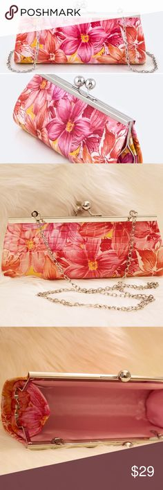 """Snake Floral Clutch The Snake Floral clutch has a little something for everyone! Vegan leather shaped like snake skin with a large floral design exterior and soft pink interior. Detachable chain allows your to the option to carry the clutch or wear it traditionally.   • Length 9"""" 