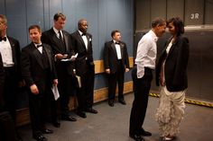 Secret Service agents avert their eyes as the Obamas share a private moment on Inauguration Day 2009.