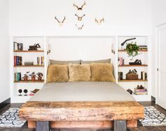 Modern white hipster bedroom with wooden bed, antlers and skulls, and fur pillows by Antonio Martins Interior Design Inc
