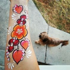 Flowers and hearts arm painting by Glitter Goose! Mini photbomb by my yorkie, Buddy. Flower heart one stroke face paint painter.