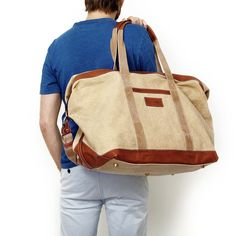"""Travelteq 'Voyager' Travel Bag - This bag is made from """"the strongest canvas and Florentine Vacchetta leather,"""" and is lined with vibrant orange fabric that bathes your neatly folded accoutrements in warmth.   #Style #Bags #Travelbags  """