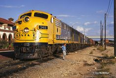 https://flic.kr/p/RNW1PL | Yellowbonnet East | On September 24, 1973, Santa Fe 346 East has stopped at Temple, Texas, for a crew change. The freshly-painted unit had just been released from Cleburne Shop a few days prior, and would run for just over a year before its retirement for the CF7 program. Photo by Joe McMillan.