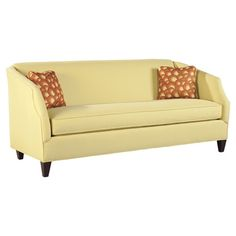 Yellow upholstered sofa with firm cushion seating and exposed wood feet. Includes two patterned accent pillows.    Product: Sofa and t...