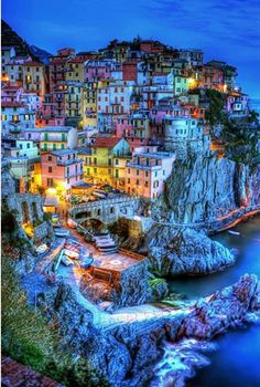 Cinque Terre, Italy. This part of Italy looks really fascinating, with the different colored buildings being illuminated by the town lights at night. It would be amazing to visit this location.