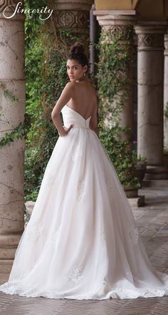 Style 4036: Romance is defined in this tulle ball gown. The gown is lined in Charmeuse to feel as good as you look. A pleated tulle bodice is accented with a thin hand beaded belt. Soft lace accents float down the skirt of the gown to the finished hem lace.