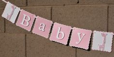 Please see shop announcement for lead time. Thank you. Perfect banner for a baby shower. OTHER COLORS AVAILABLE. Pink and white 1 row baby shower banner. 3 Giraffes included. Faux pearls are used for the eyes. Each scallop is 51/2 x 51/2 inches. Giraffes are 5 inches tall and consist of 4 layers of card stock. Banner reads Giraffe Baby Giraffe Shower Giraffe.Letters are 4 inches tall in white with a pink shadow. All lettering and giraffes are mounted in foam pop dots to give 3D ef...