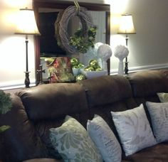 Christmas behind the couch shelf, brown couch, green, wreath on mirror