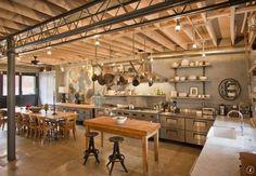 cuisine industrielle aménagée avec des meubles en bois et inox, des étagères ouvertes et un rangement à casseroles suspendu