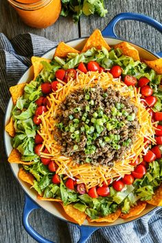 Taco Salad with Creamy Taco Dressing from afarmgirlsdabbles.com - This layered salad is bursting with fresh veggies, plus taco seasoned beef and crunchy, nacho cheese-y, irresistible Doritos. #taco #salad #beef #dressing #dorito #doritos