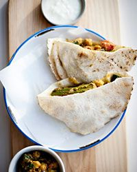 Curried Vegetable Roti | This multiculti recipe is a cross between doubles (a Trinidadian sandwich of fried bread and curried chickpeas) and a kathi roll (essentially an Indian wrap). Grace Parisi folds Indian roti bread around a filling of zucchini, okra, chickpeas, tomato and spinach in a creamy, tangy, curried yogurt sauce.