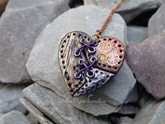This intriguing Steampunk broken heart necklace is made from Polymer Clay. The parts, textured to resemble wood, copper and steel are mended