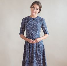 This pretty dress is made from a navy cotton fabric with lovely floral print. The fitted bodice has a round neck and peter pan style collar with blue piped edging. The skirt has several pleats at both the front and back and in seam pockets. Concealed zip fastening down the back. All