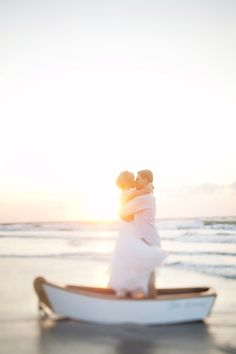 Beach Themed Wedding - LOVE this shot of the bride & groom kissing with the sun setting behind them. Picture perfect!