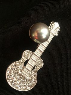 Check out this item in my Etsy shop https://www.etsy.com/listing/271137508/guitar-brooch-with-swarovski-and-blue