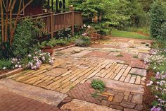 This patio was created from recycled materials. Just as a quilter sews together fabric pieces, these homeowners married stone, brick, and cobble to create a charming space.