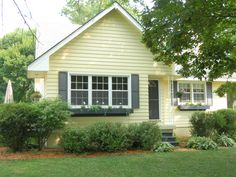 Yellow house with black shutters, door, window boxes. Hmmmm my house is yellow.