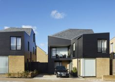 London firm Alison Brooks Architects used dark-stained timber and sloping rooftops to reinterpret the rural architecture of Essex for this suburban housing development