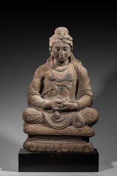 Bodhisattva assis en padmasana, il tient le vase à eau qui l'identifie à Maitreya.  Il porte la parure des Bodhisattva : le collier plat, le sautoir, le cordon-reliquaire, le brassard, les bracelets et les pendants d'oreille.  Il est vêtu du paridhana et de l'uttariya qui laisse le torse dénudé. La chevelure ondulée, maintenue par une résille, chignon au sommet du crâne. En schiste.  H : 41 cm.  Art gréco-bouddhique du Gandhara (Ier-Ve s.)