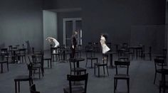 Example of how minimalist or stylised scenography can contrast with costume and physicality to convey meaning or atmosphere.