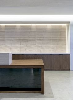 For the lobby, O+A custom- designed a geometric limestone wall with local fabricator De Anza Tile. Durable, classic materials such as limestone, walnut, glass, and steel convey a sense of stability and timelessness to clients. (Courtesy Studio O+A)