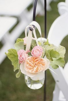 Ceremony flowers--lining the aisle with mason jars with flowers hanging on shepards hooks by ribbon.