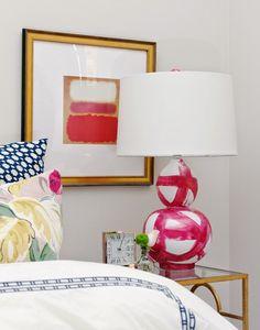 brass nightstand, lamp, mixed prints, linen, wide mat on artwork
