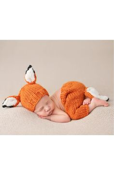 Bundle up the newborn in this adorable hat-and-pants set knit from soft, cozy acrylic and decked out with fox ears and tail for charming woodland style.