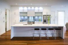 un îlot de cuisine blanc et élégant avec quatre chaises de bar noires