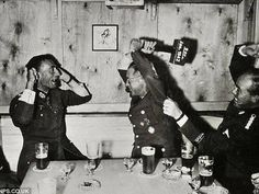 """Nazi officers enjoy a drunken game of """"who-knows-what"""" in an Oslo bar in 1942."""