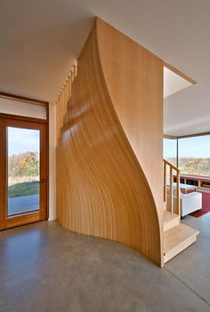 Inside this house, a staircase is screened behind an undulating timber wall