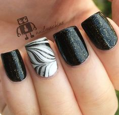 Beautiful black feather nail art design. Combined with a sandwich gold glitter paint design, this nail art combines the soft and elegant touch of the feather and glitter effect.source