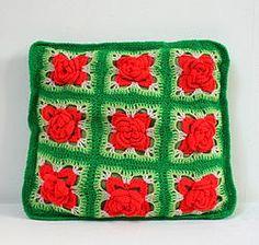 Coussin vert et rouge : Petit coussin décoratif super vintage, en tissus vert d'eau, entièrement recouvert de laine crochetée : carrés de fleurs orangées en volume d'un côté, tricot vert de l'autre.