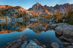 Leprechaun Lake Sunrise - From a rocky peninsula on the shore of the Enchantment's Leprechaun Lake, Prusik Peak surrounded by the alpine glow of sunrise and golden larches is reflected in the blue waters.  Autumn is the ideal time to visit the Enchantments when the larches turn bright gold.  This images is from my six day backpacking trip in early October of this year.  Thanks for viewing my image.  Prints available at www.erwinbuske.com