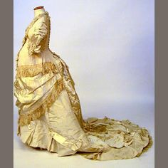 c. 1880s ___ A one-piece maternity trained wedding gown, of cream finely ribbed silk and ivory satin, with silk fringe and cord detailing, lace trimmings to collar and cuffs, together with a white cotton trained petticoat with bobbin lace detailing. ___ from Bonhams auction, 16 Dec 2003