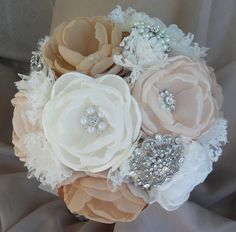 Vintage fabric bouquet - coral shades, ivory, tan and champagne loaded with crystals and brooches, via Etsy.