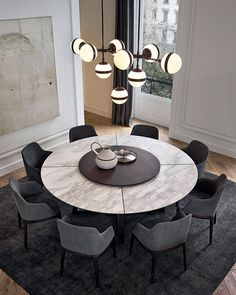 Concorde table in spessart oak, top in mat calacatta oro marble with central spinning tray in spessart oak. Grace armchairs in spessart oak and 5 grafite Nabuk leather. Onda pouf in 1401 oliva Persia removable velvet.