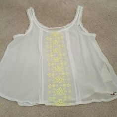 Flash Sale! Hollister sheer cami w/ yellow flower Brand new never worn Hollister sheer camisole with pretty yellow floral embroidery down the front. Size small. The price tag fell off but the plastic is still attached to the Hollister tag. Beautiful paired with a lace tank top underneath and skinny jeans. No paypal or trades. Hollister Tops Camisoles