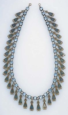 Edwardian. A RARE GREEK REVIVAL MOONSTONE AND ENAMEL NECKLACE, BY LOUIS COMFORT TIFFANY, TIFFANY & CO. Designed as a series of moonstone collets, suspending gold wirework plique-à-jour green enamel fringe, mounted in silver and gold, circa 1910, 18½ ins.