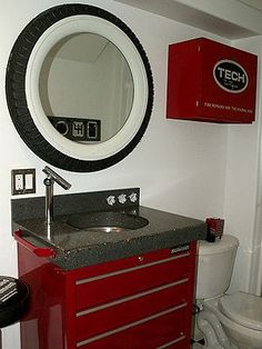 Shelley and Guy Chomistek of Rafter C Precast Concrete- bathroom project incorporating a wide variety of auto parts into their design, like the shock stool and radial repair kit, custom-made mirror fashioned from a Model A whitewall tire & gearshift towel hooks (seen in the mirror reflection.).