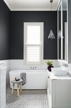 Creative Ideas For A Bathroom Makeover: Black and white all over. The black and white combo has been gaining steam in the bathroom. White subway tile and charcoal gray paint on the walls is chic on its own, but patterned black and white tile on the floor takes it to the next level. Finish on a strong note with an on-trend two-tone stool, graphic towel and maidenhair fern in a black pot.