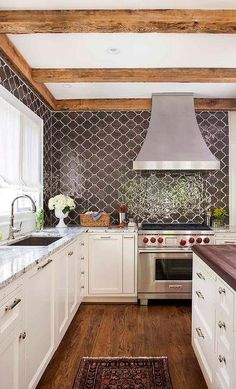 Black cooktop backsplash tiles gorgeously display an arabesque pattern with white grout to truly make a contrast pop! A stainless steel vent hood over a wolf range upgrades the appliances and stands out against the white and brown wood tones.