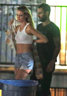 Behati Prinsloo revealed her midriff while filming a Maroon 5 music video with her husband Adam Levine.