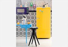 Os enfeites de pinguins completam o visual desta geladeira vintage amarela. Os móveis com pés palito e o micro-ondas, que também têm design retrô, entram no clima. As cores vibrantes deixam o ambiente moderno e descontraído