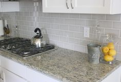 A soft grey subway tile #backsplash contrasts nicely with white #kitchen cabinets.