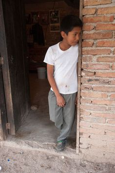 Forty-three male students from the Raul Burgos Rural Teachers College in Ayotzinapa, Guerrero were disappeared on September 26, 2014 at the hands of local police working in conjunction with drug traffickers. Brian Gaspar de la Cruz, brother of missing student Emiliano Gaspar de la Cruz, stands in the doorway of the family's home in Omeapa, Guerrero.