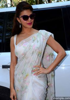 Jacqueline Fernandez puts the oomph in a white Shehla Khan sari with a low cut sleeveless blouse paired with Shruti Sushma jewellery, pink lipstick, pink nail polish and cat eye sunglasses. via Voompla.com