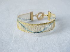 bracelet, handmade bobbin lace out of yarn, gold-blue, gold coated fastener, klöppeln, dentelle, spitze, boll...