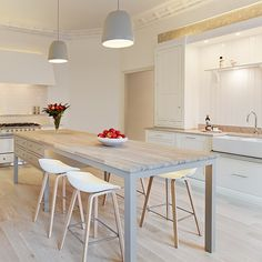 White kitchen with white cabinetry, white splashback tiles, butler sink, white range cooker and neutral cook's table