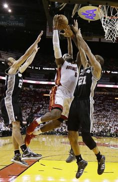 LeBron James drives to the basket on Tim Duncan and guard Manu Ginobili during the first half of Game 6 of the 2013 NBA Finals basketball